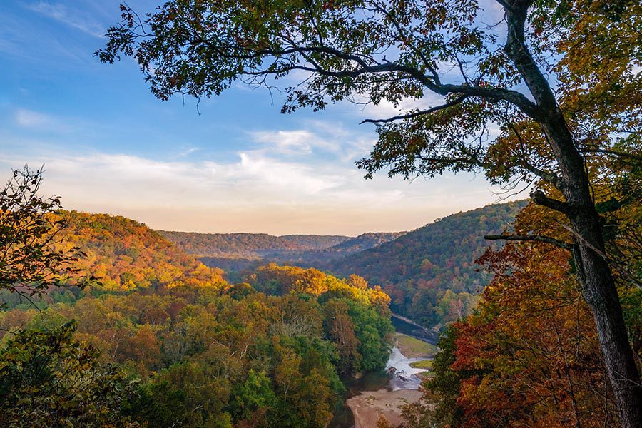 Blog - Mammoth Cave National Park, Seen From an Overlook, the Mountains Stretching Into the Distance, Trees Turning Orange, a Bright Blue Sky Overhead