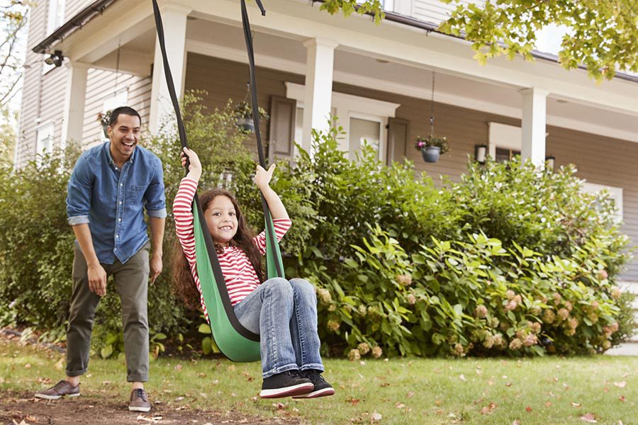 Blog - Dad Pushing His Daughter on a Green Fabric Tree Swing In Their Front Yard