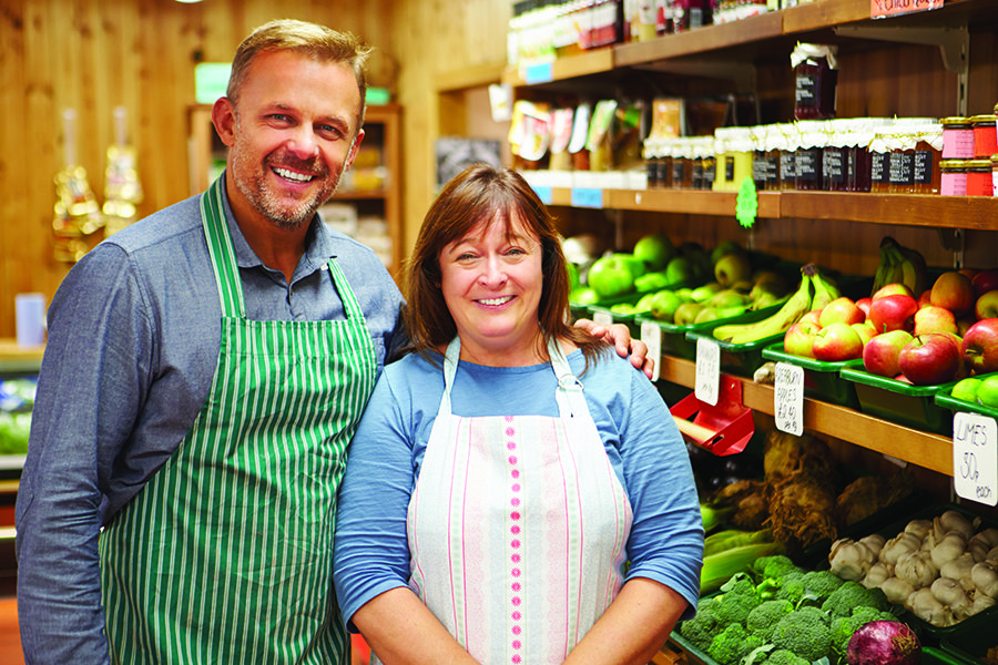 Client Center - Grocery Store Owners Pose in Front of the Produce Section, Wearing Aprons