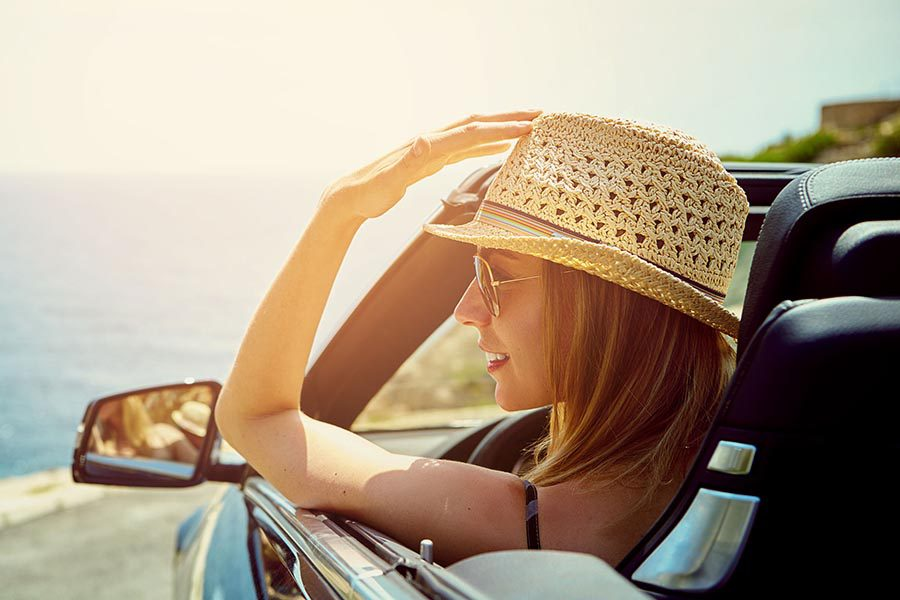 Contact - Woman Wearing Straw Hat and Sunglasses, Parked in Front of a Lake in a Convertible