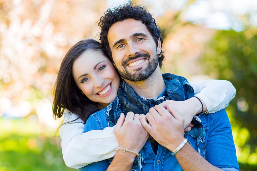 Personal Insurance - Young Couple Smiling, Wife Wrapping Her Arms Around Her Husband, Wearing Warm Blue and White Clothing