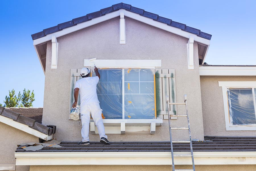 Specialized Business Insurance - Contractor Installing Windows and Painting Trim On a Stucco Home