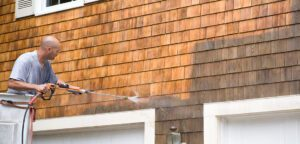 man hosing down the side of his house