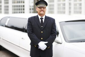 photo of a white limo with a Chauffeur standing in front of the limo