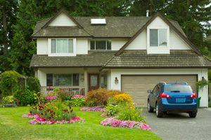 picture of a home with a blue car in the driveway