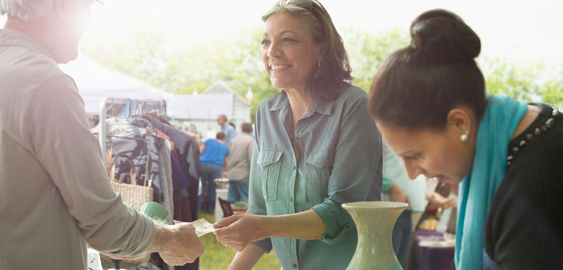 young woman purchases vase at garage sale while her friend looks on