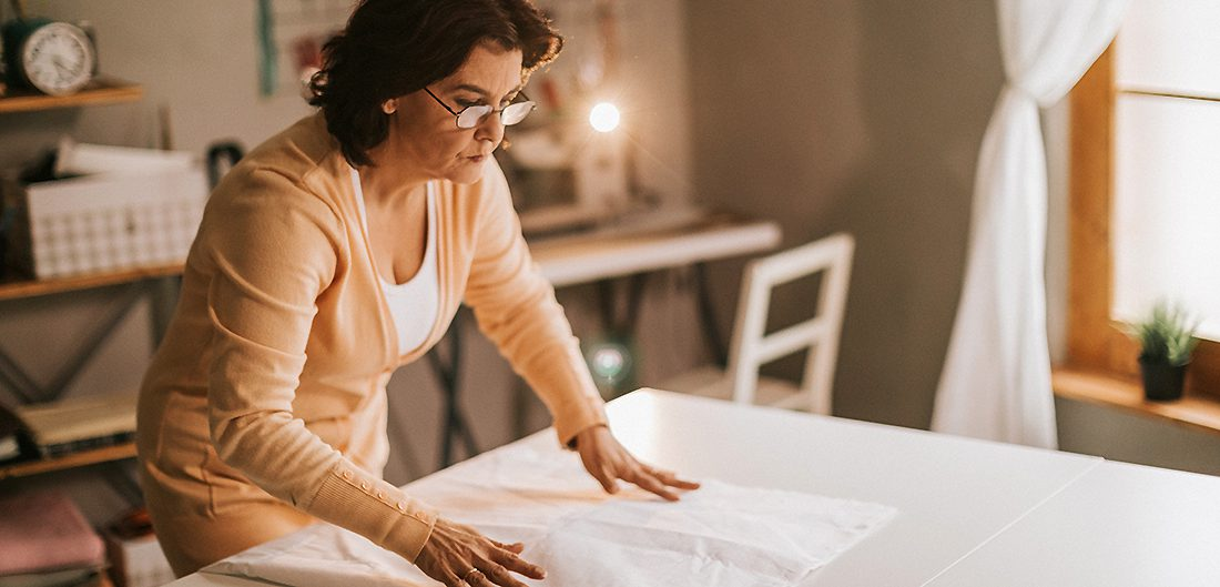 middle aged woman lays down fabric in craft room