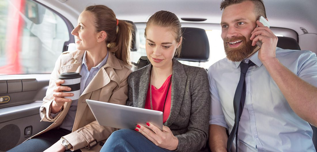 Three business people sitting in the back of a car