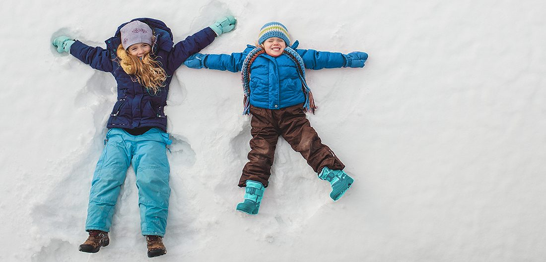 two young children make snow angels