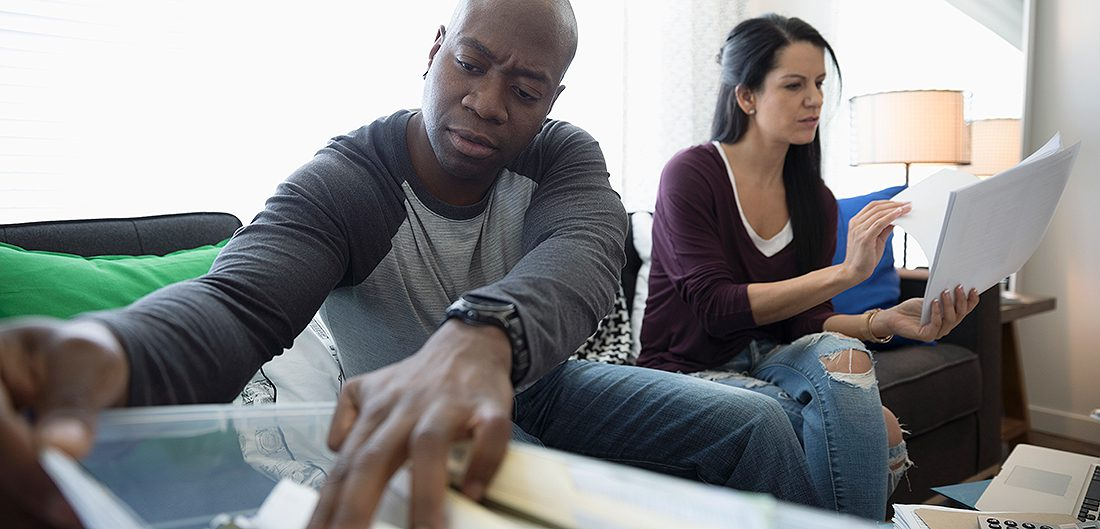 man and woman search through file folders in living room