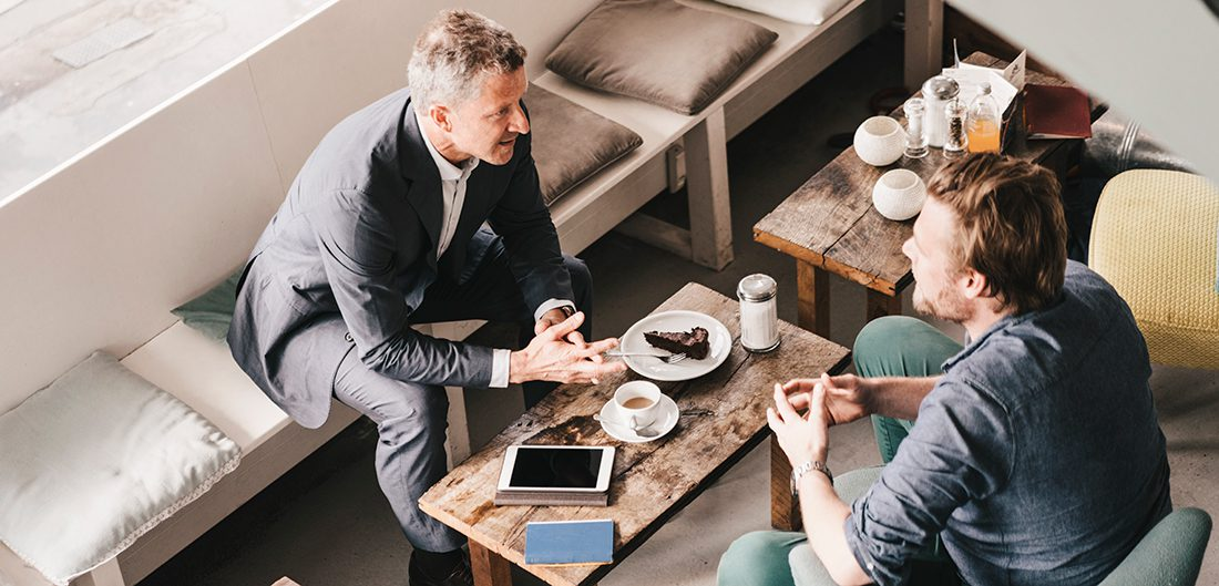 middle aged businessman talks with young businessman at trendy coffee shop
