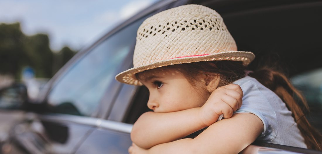 little girl leaning out car window
