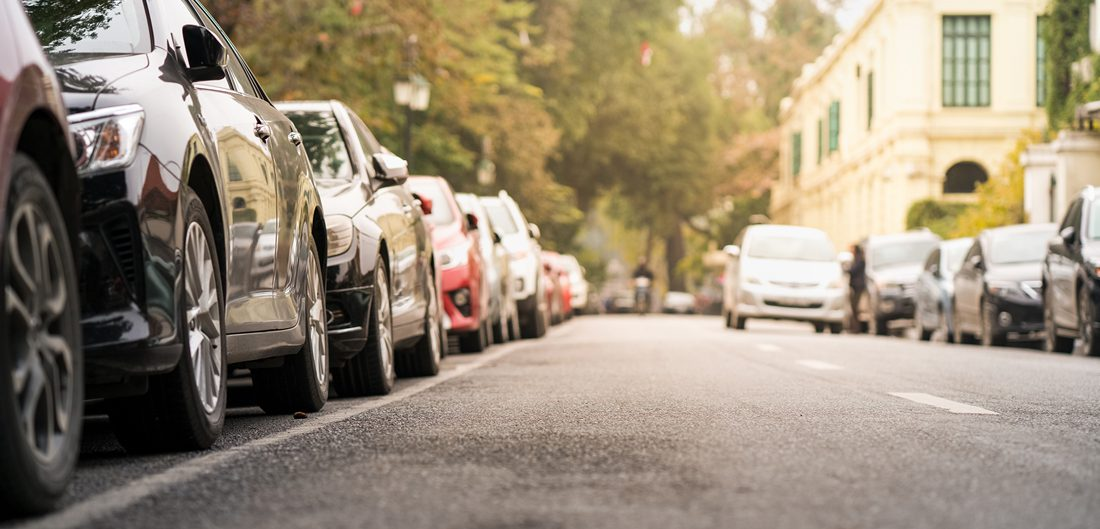 many cars are parallel parked on city street