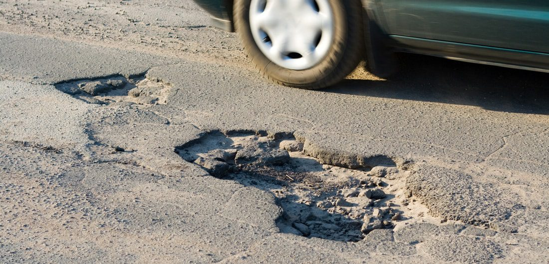 car driving by a pothole