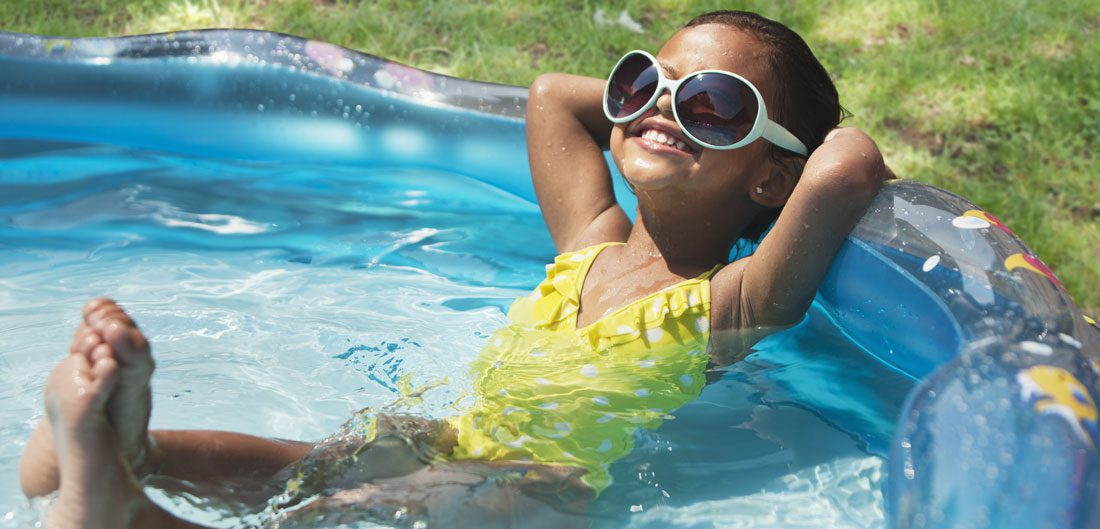 young girl relaxes with sunglasses in kiddie pool