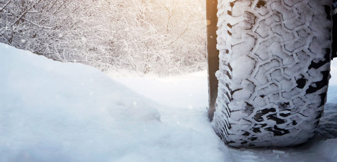 snow-covered tire drives over snow