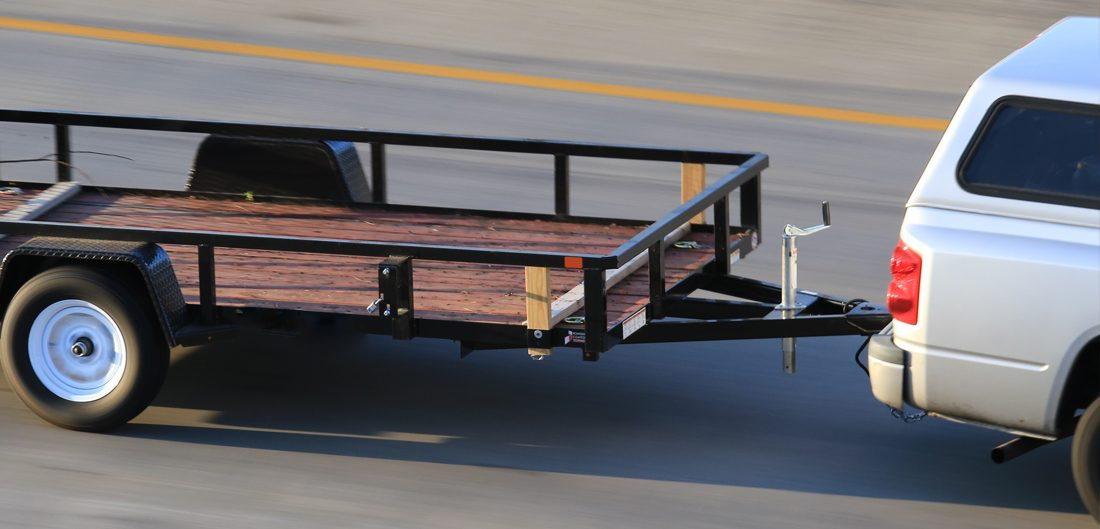 truck tows flat trailer on highway