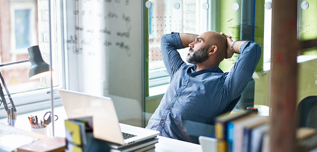 man reclines at desk, looking thoughtfully out window