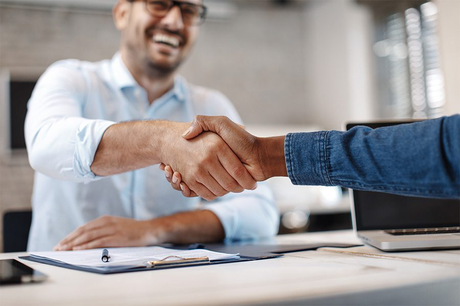 About Our Agency - Close up of a Handshake between Business Colleagues in the Office with a Focus on the Handshake and the Colleague and Background Blurred