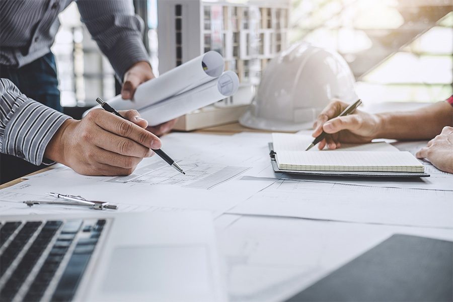 Specialized Business Insurance - Closeup of an Architect and Engineer Working Together on a Blueprint for a Project