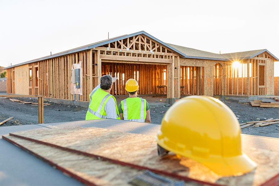 Contract Bonds - View of Two Contractors Standing on a Residential Jobsite Looking at a New Home Build