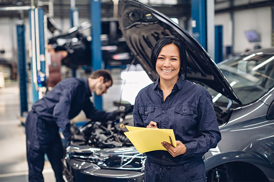 Miscellaneous PA Motor Vehicle Business Bonds - View of a Female Mechanic Holding Paperwork and Standing in Front of a Car in a Garage Repair Shop