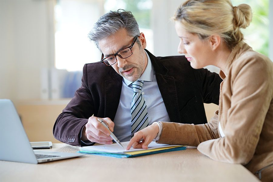 Notary Errors and Omissions Liability Insurance - View of a Mature Businessman and Client Sitting in an Office Going Through Paperwork Together