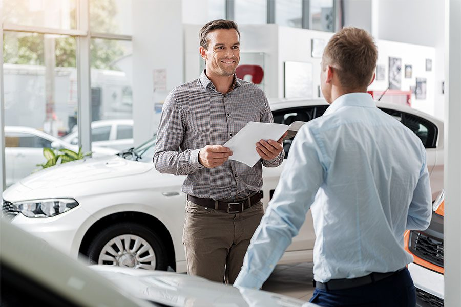 Pennsylvania Motor Vehicle Bonds - View of a Smiling Car Salesman Standing in a Car Showroom While Talking to a New Client
