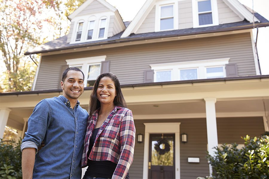 Personal Insurance - View of a Smiling Young Married Couple Standing in Front of Their New Two Story Home