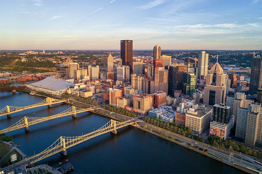 Pittsburgh PA - Aerial View of Downtown Pittsburgh Pennsylvania Next to the River on a Cloudy Sky at Sunset