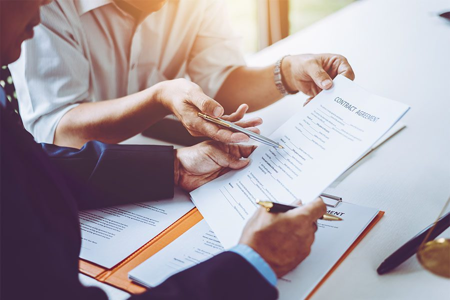 Public and Independent Adjuster Bonds - Closeup View of an Agent and Client Going Through a Contract Together in the Office