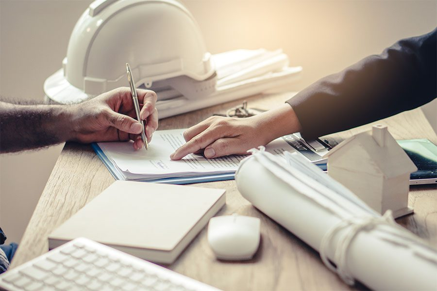 Specialized Business Insurance - Closeup View of Contractor Signing Paperwork with a Business Woman in the Office