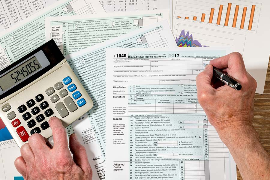 Tax Preparer Insurance - Closeup View of a Tax Preparers Hands Working on Tax Documents and Using a Calculator
