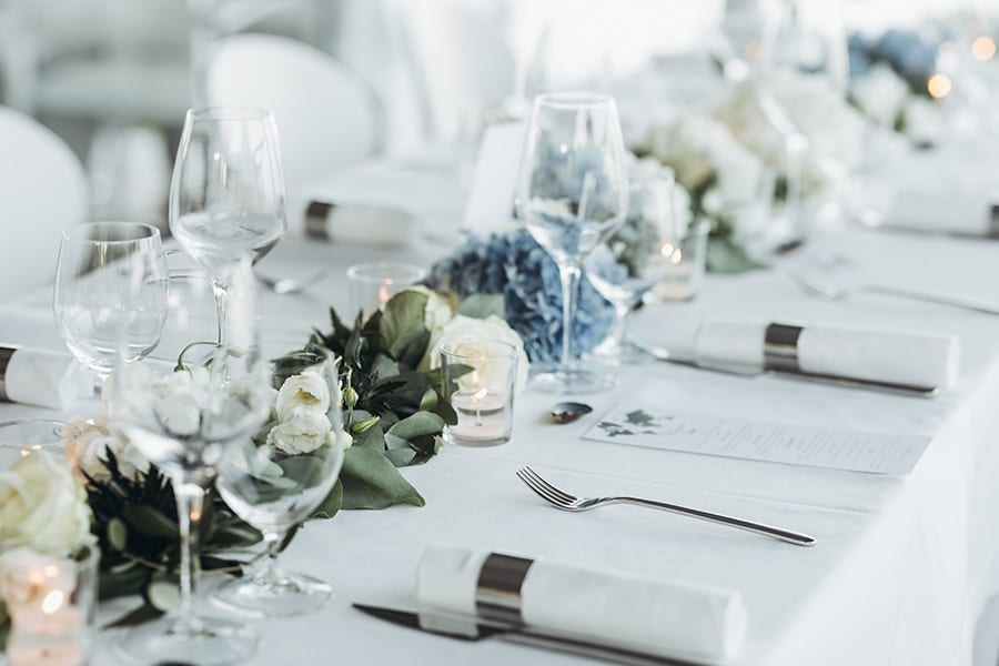 Special Event Insurance - Wedding Table Decoration with Floral Garland and Blue Flowers Between Glasses on a White Tablecloth
