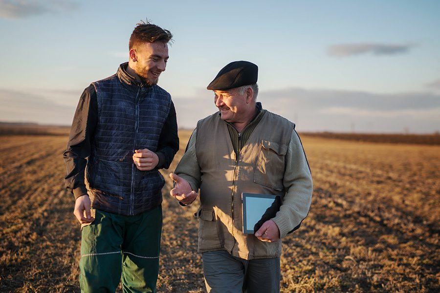 About Our Agency - Father and Son Farmers Standing Together on a Field Smiling and Talking With Each Other During Sunrise