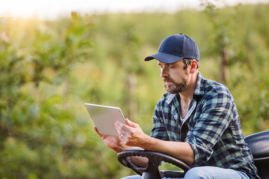 Client Center - A Farmer With His Tablet Sitting on a Mini Tractor Outdoors in His Orchard