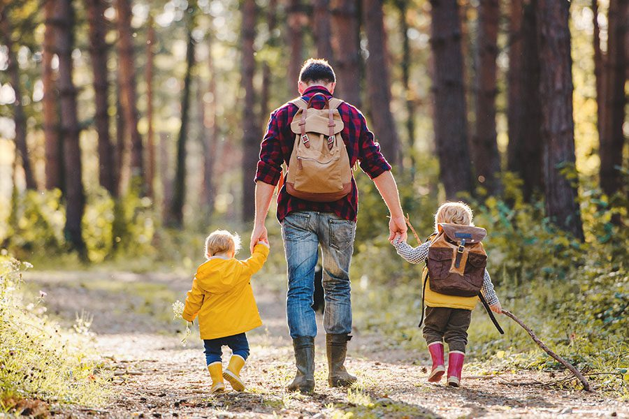 Employee Benefits - A Rear View of a Father With His Toddler Children Walking in an Autumn Forest