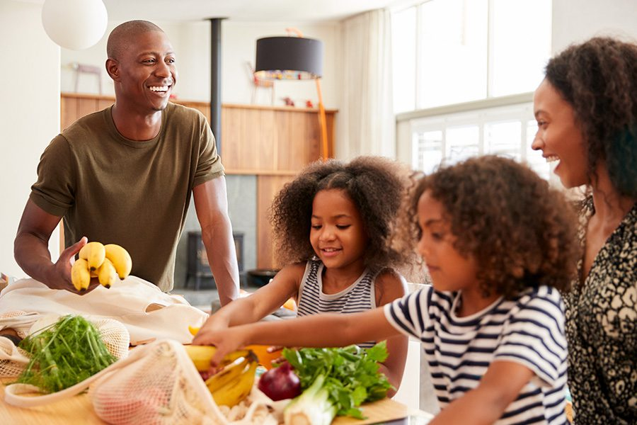 Personal Insurance - Family Returning Home From a Shopping Trip Unpacking Plastic-Free Grocery Bags in Their Kitchen