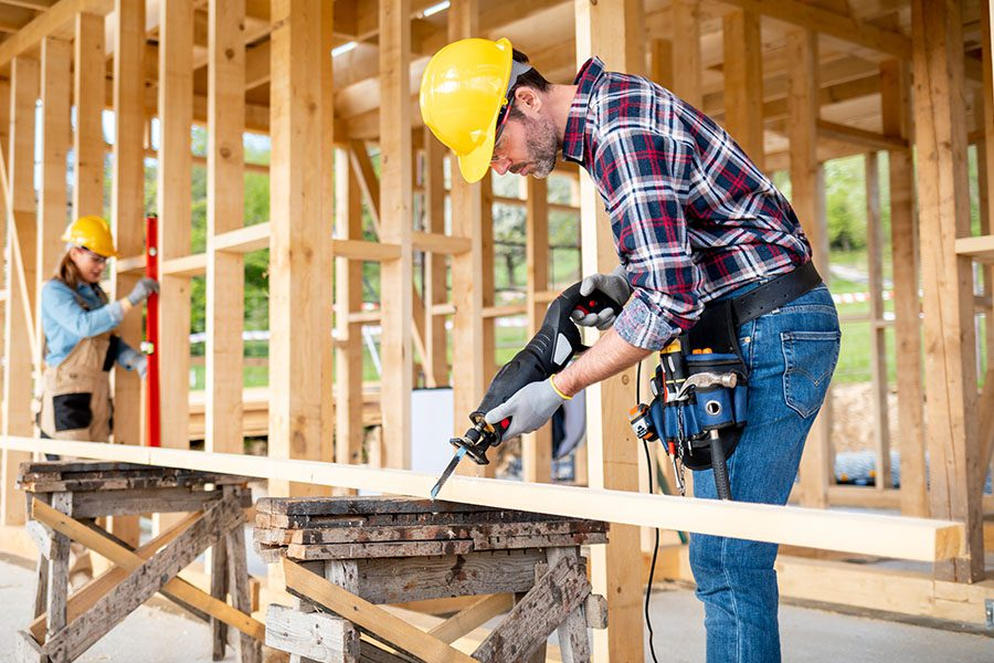 Specialized Business Insurance - Team of Workers Doing Woodwork at a Construction Site of a Wood Frame House