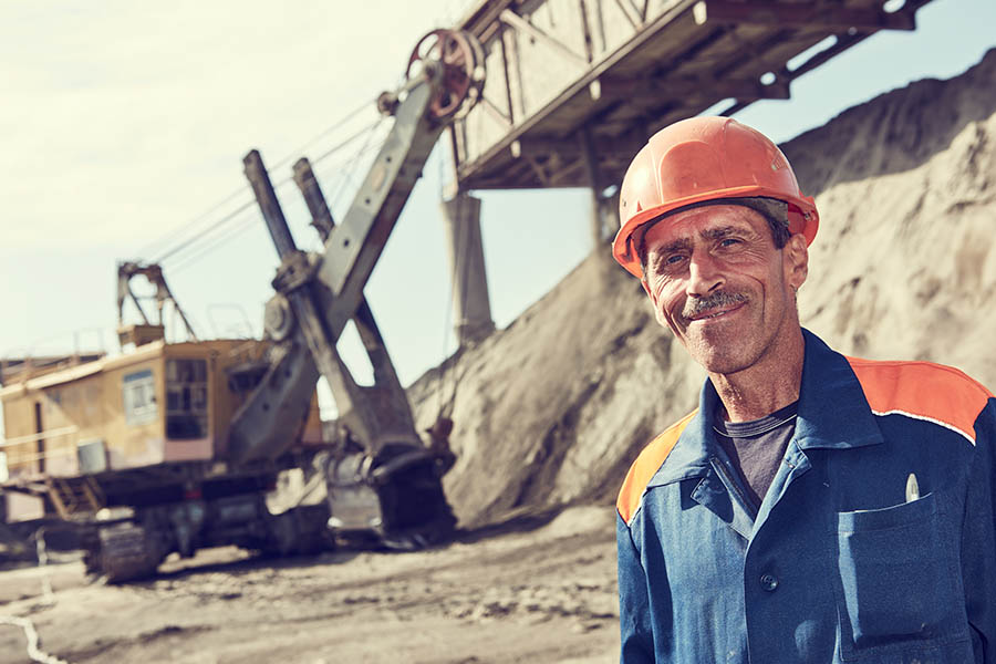 Mining Insurance - Mining Worker Standing in Front of a Heavy Excavator Loading Gravel into a Train Container