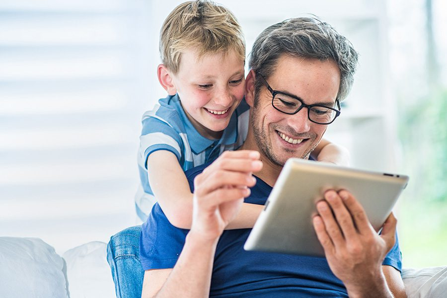 Client Center - A Father and His Young Son Are Having Fun Using a Tablet Together
