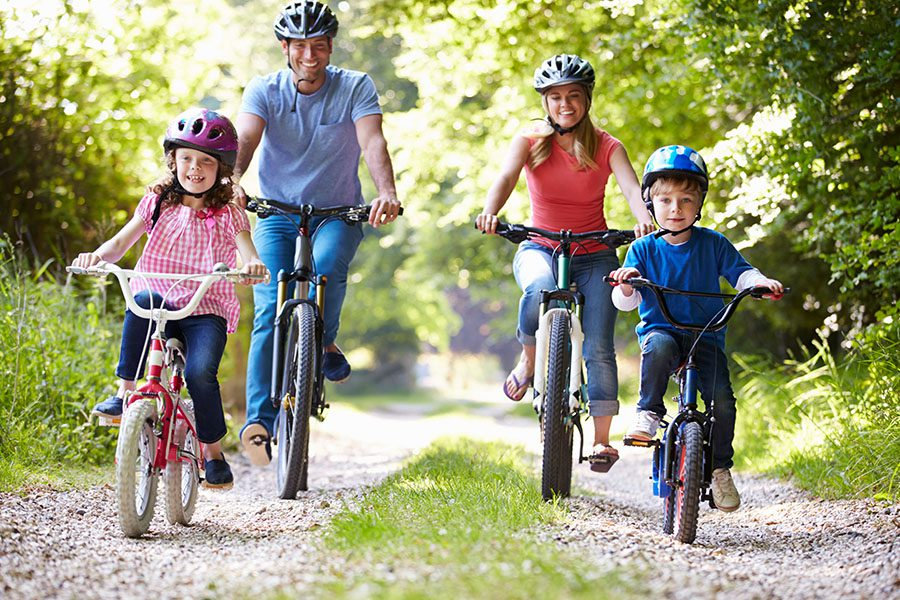 Employee Benefits - A Happy Family of Four Are Riding Their Bikes on a Dirt Road in the Countryside on a Sunny Day