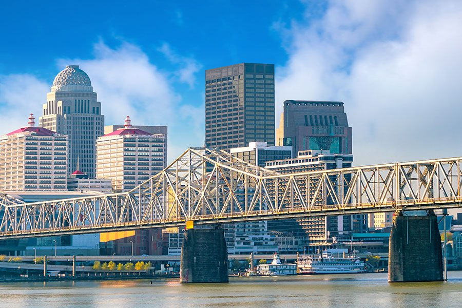 Louisville, KY - Long Distance Skyline View of Downtown Louisville, KY Displaying Large Business Buildings and a Bridge Crossing a River