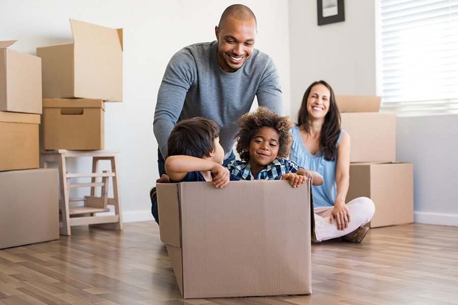 Personal Insurance - A Father Playing and Pushing His Children in a Box on the Floor on Moving Day While His Wife Watches and Smiles