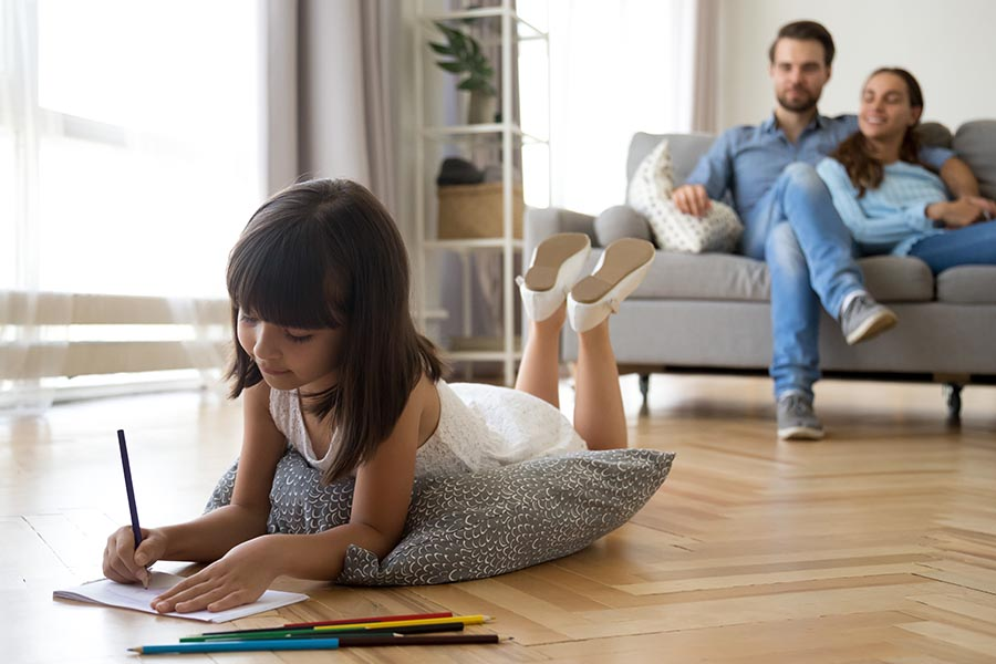 About Our Agency - Family in the Living Room at Home with Young Daughter Lying on a Soft Cushion on the Floor with Parents Sitting on the Sofa