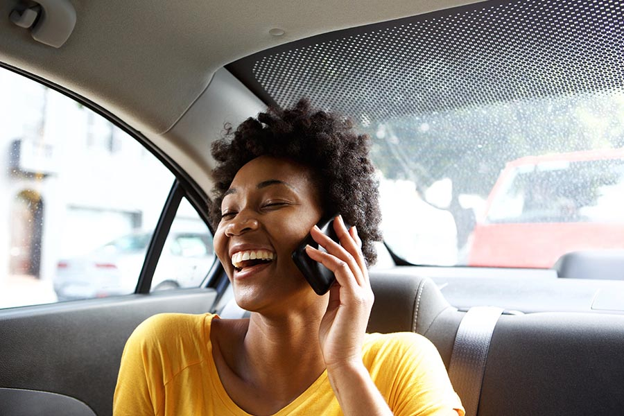 Client Center - Laughing Young Woman in a Car Talking on Her Mobile Phone