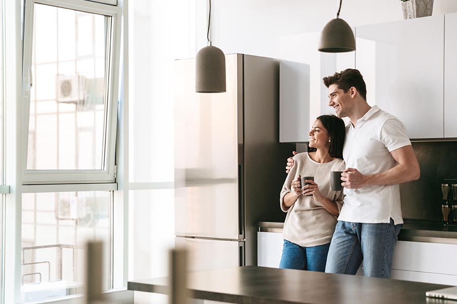 Personal Insurance - Happy Young Couple Holding Coffee Mugs and Looking Out the Window of a Modern Kitchen in Their New Home