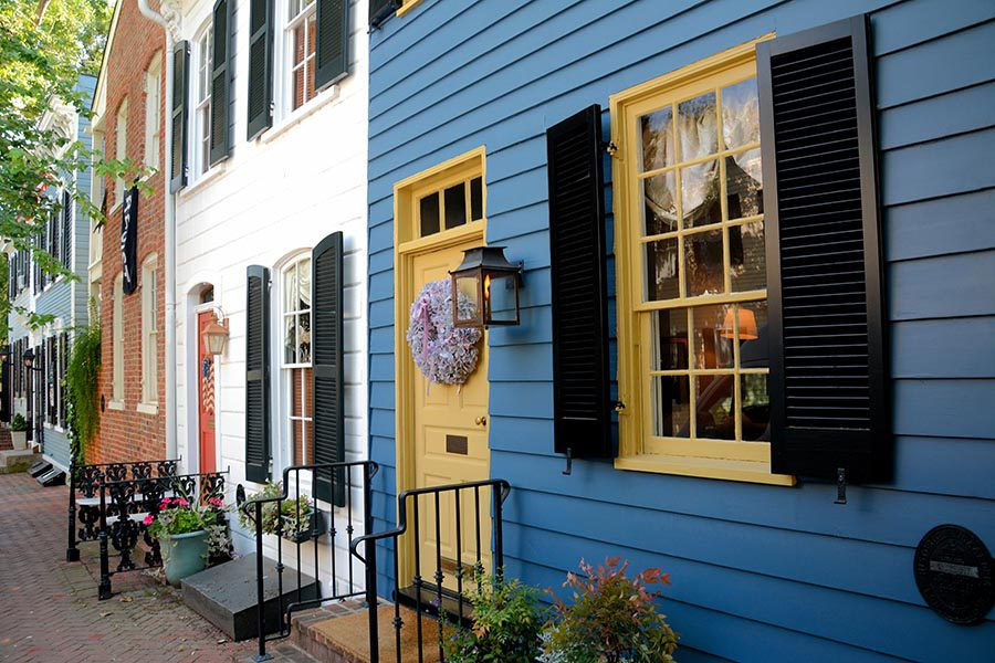 About Our Agency - Old Town Alexandria, Virginia Row Homes Painted in Bright Colors, With Brick Sidewalks and Wooden Shutters