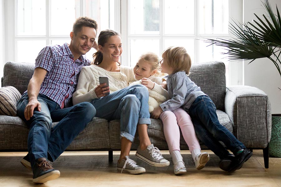 Blog - Young Family Sitting Close On Their Sofa Using a Smartphone