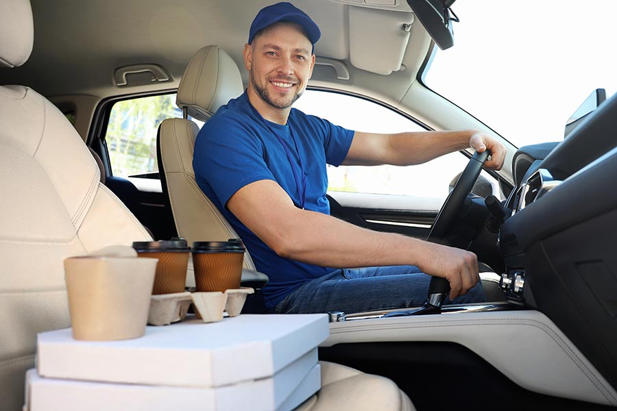 Business Insurance - Food Delivery Driver Wearing Blue Shirt, Driving His Car, Food Packages Sitting on the Passenger Seat